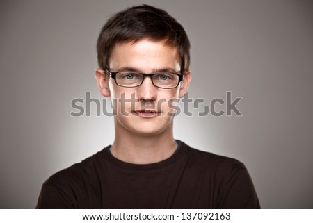 Attractive young man in studio looking at camera/ Portrait of a normal boy on a grey background - stock photo
