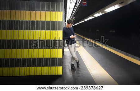 Attractive young man in train or underground station using cellphone (mobile) - stock photo