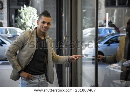 Attractive young man in urban setting, pointing finger at clothes in shop window, smiling at camera - stock photo
