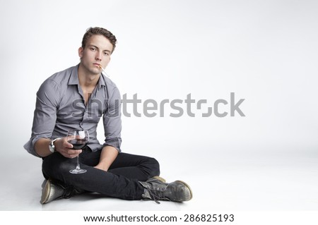 Attractive young man is sitting on the floor with a drink in his hand - stock photo