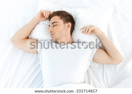 Attractive young man is sleeping in his bed. He is lying in his bed with relaxation - stock photo