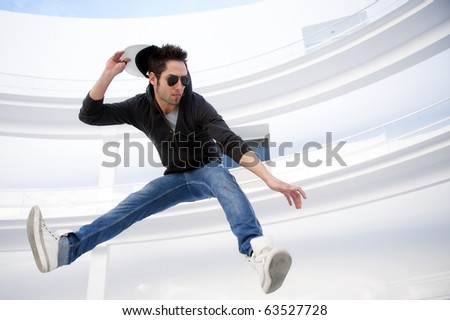 Attractive young man jumping in urban and modern background - stock photo