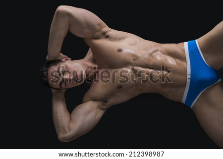 Attractive young man laying on the floor with naked muscular ripped body, hands under head - stock photo