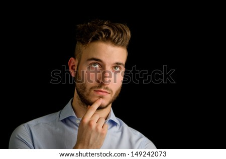 Attractive young man looking up, thinking, isolated on black background - stock photo