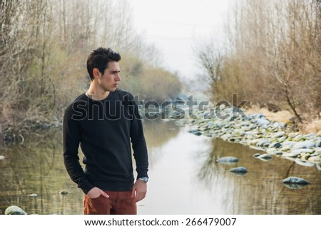 Attractive young man outdoor in nature, at river or water stream, looking away to a side at large copyspace - stock photo