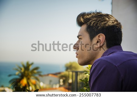Attractive young man outdoor looking over a seaside landscape with sea in background with a serious expression - stock photo