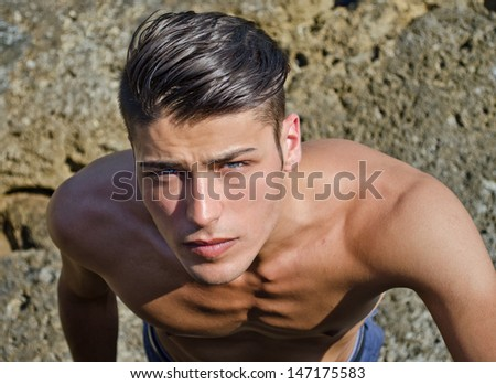 Attractive young man outdoors looking up in camera, shirtless - stock photo