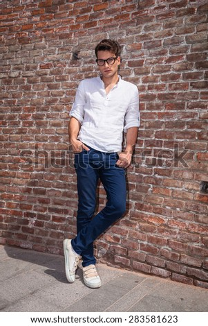 Attractive young man posnig with his hands in pockets while leaning on a brick wall/ - stock photo