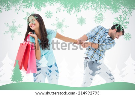 Attractive young man pulling his shopaholic girlfriend against snowflakes and fir tree in green - stock photo