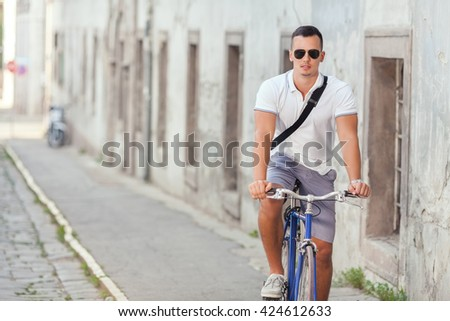 Attractive young man riding a bicycle on the old town street on a sunny summer day - stock photo