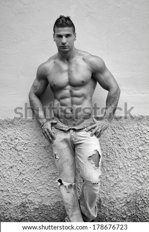 Attractive young man shirtless with jeans leaning against a wall, black and white shot - stock photo