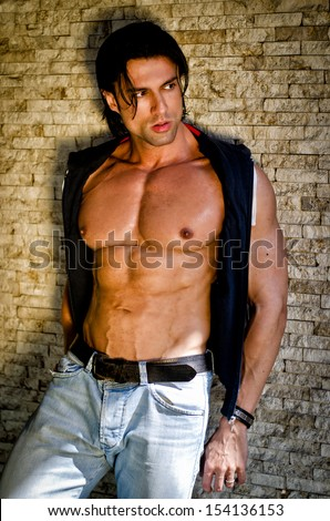 Attractive young man shirtless with jeans leaning against a wall looking to a side - stock photo