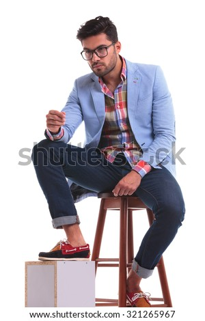 Attractive young man sitting on a chair while holding one leg on a wood box. - stock photo