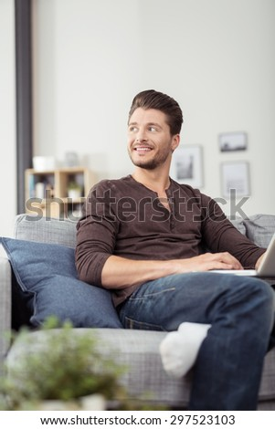 Attractive Young Man Sitting on Couch with Laptop Computer, Looking Into Distance with Happy Facial Expression. - stock photo