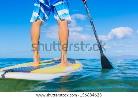 Attractive Young Man Stand Up Paddle Surfing In Hawaii, Beautiful Tropical Ocean, Active Beach Lifestyle - stock photo