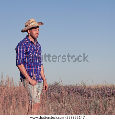 Attractive young man standing in a field. Cowboy - stock photo