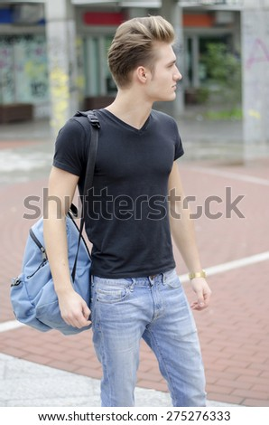 Attractive young man wearing black T-shirt and jeans with back pack standing outside - stock photo