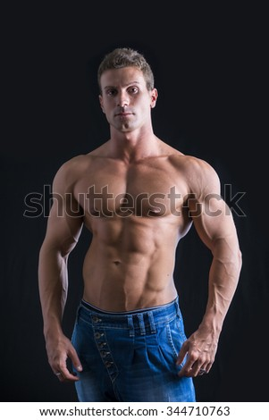 Attractive young man with naked muscular torso, wearing jeans, isolated on black background - stock photo