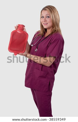 Attractive young medical worker wearing maroon scrubs with stethoscope holding up a red hot water bottle - stock photo