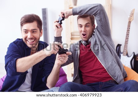 Attractive young men are playing video-game - stock photo