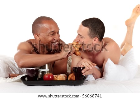 Attractive young mixed ethnicity gay, homosexual couple, Caucasian and African American men in the bedroom, grooming, enjoying breakfast.  Studio, white background. - stock photo