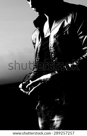 Attractive young muscle male model posing outdoors in black shirt and leather jacket.Fashion colors  - stock photo