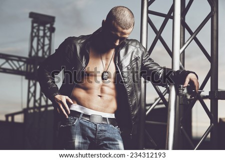 Attractive young muscle male model posing outdoors in  leather jacket.Fashion colors  - stock photo