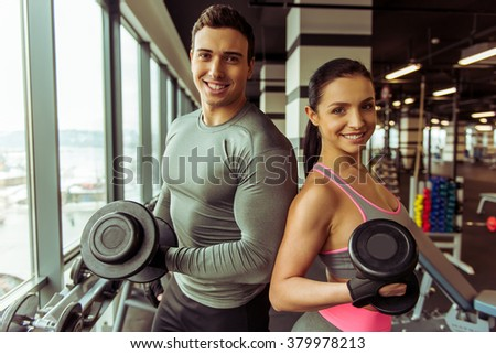 Attractive young muscular people working out with dumbbells in gym, looking at camera and smiling - stock photo