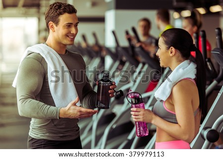 Attractive young people drinking water, talking and smiling while standing in gym - stock photo