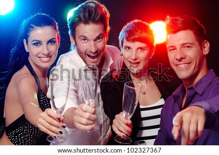 Attractive young people having fun in nightclub, smiling, drinking champagne. - stock photo