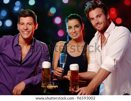 Attractive young people smiling, drinking in nightclub.? - stock photo