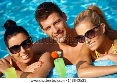 Attractive young people smiling in swimming pool, drinking cocktail. - stock photo