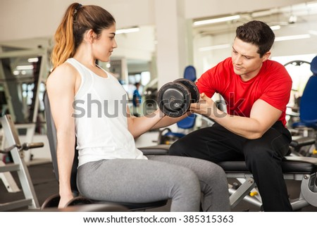 Attractive young personal trainer helping a young woman with her posture while she lifts some weights at a gym - stock photo