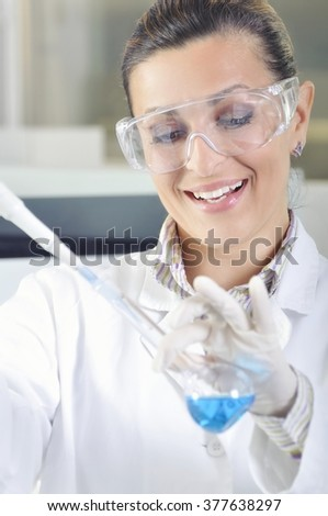 Attractive young PhD student scientist observing the blue indicator color shift after the solution destillation in chemical laboratory - stock photo