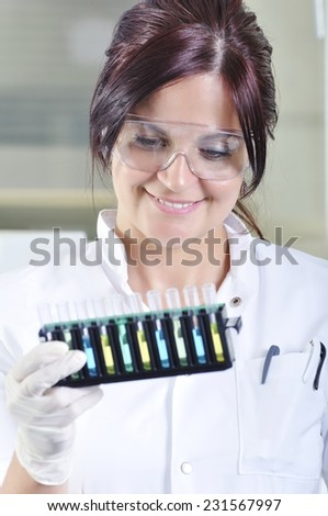 Attractive young PhD student scientist observing the blue, yellow and green indicator color shift after the solution destillation in chemical laboratory - stock photo