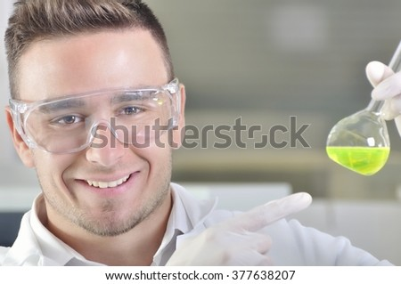 Attractive young PhD student scientist observing the green indicator color shift after the solution destillation in chemical laboratory - stock photo
