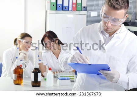 Attractive young PhD student scientist with two colleague out of focus behind him in chemical laboratory - stock photo
