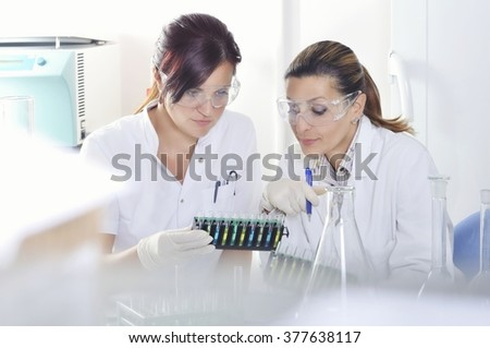 Attractive young PhD students scientists  observing the blue, yellow and green indicator color shift after the solution destillation in chemical laboratory - stock photo