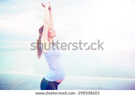 Attractive young pregnant woman doing breathing exercises at the seaside standing with her arms raised above her head and eyes closed in a fitness and health concept - stock photo
