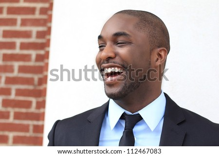 Attractive, Young Professional African American Businessman Smiling and Laughing  While Looking to the Side and Wearing a Black Suit and Tie - stock photo