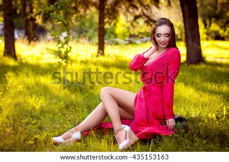Attractive young red hair woman with beauty makeup siting and posing in red dress. Outdoor - stock photo