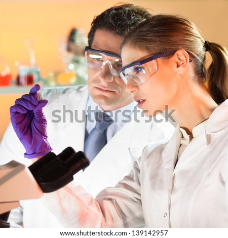 Attractive young scientist and her post doctoral supervisor looking at the microscope slide in the forensic laboratory. - stock photo