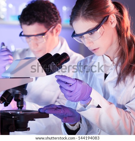 Attractive young scientist and her post doctoral supervisor working on a project in the life science laboratory. - stock photo