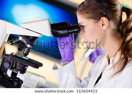 Attractive young scientist looking at the microscope slide in the forensic laboratory. - stock photo