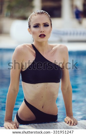 attractive young sexy and beautiful woman in black bikini by the pool. blue water and hot summer  - stock photo