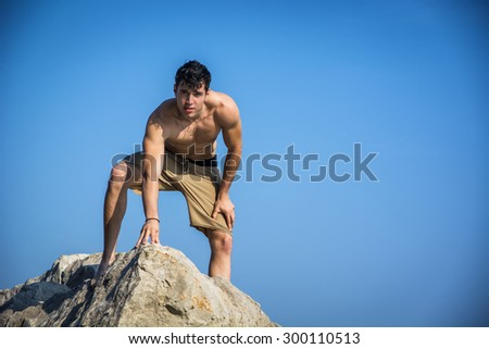 Attractive young shirtless athletic man climbing on rock by water on ocean or sea shore, wearing shorts, looking at camera - stock photo