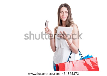 Attractive young shopaholic with credic card looking on digital tablet and carrying shopping bags isolated on white with copyspace - stock photo