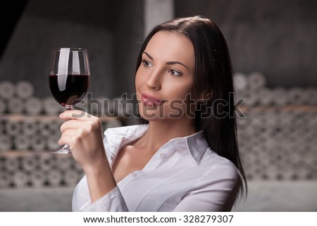 Attractive young sommelier is analyzing the quality of red wine. She is holding glass and looking at drink with interest. The woman is standing in cellar and smiling - stock photo