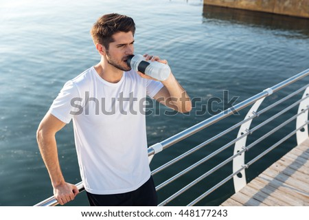 Attractive young sportsman standing on wooden terrace near the sea and drinking water - stock photo