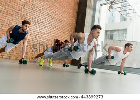 Attractive young sportsmen exercising with dumbbells - stock photo